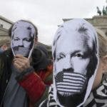 People wear paper masks to protest against a possible extradition of WikiLeaks founder Julian Assange to the USA in front of the Brandenburg Gate in Berlin, Germany, Thursday, May 2, 2019. (Wolfgang Kumm/dpa via AP)
