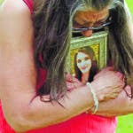 ADVANCE FOR RELEASE AT 12:01 A.M. JUNE 18, 2019 AND THEREAFTER -  Melany Zoumadakis clutches a photo of her daughter, Tanna Jo Fillmore, on Friday, April 26, 2019, in Salt Lake City. Fillmore killed herself in the Duchesne County Jail in 2016, after repeatedly calling her mother, saying she was being denied her prescription medicines that had stabilized her. Her mother has filed suit. (AP Photo/Rick Bowmer)