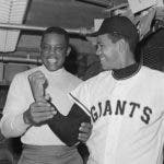 (Original Caption) Willie Mays, (L), of the Giants, checks the pitching arm of Giant pitcher Juan Marichal, after the latter arrived for his first workout of the season.