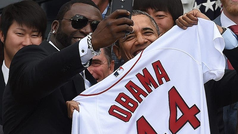 Red Sox Designated Hitter David Ortiz (L) takes a selfie with US President Barack Obama after presenting his a jersey during a ceremony on the South Lawn at the White House in Washington, DC, on April 1, 2014.  Obama honored the Boston Red Sox for their 2013 World Series Championship. AFP PHOTO/Jewel Samad