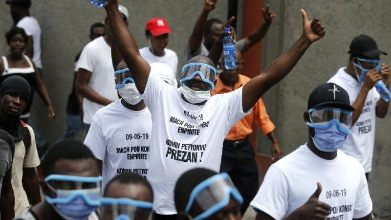Protesters gesture to the camera during a protest demanding the resignation of President Jovenel Moise in Port-au-Prince, Haiti, Sunday, June 9, 2019. The protesters are demanding further investigation into the fate of funds that resulted from subsidized oil shipments from Venezuela. (AP Photo/Dieu Nalio Chery)