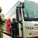 A Mexican Marine stands guard as an immigration officer boards a bus to check for migrants, near Tapachula, Mexico, Friday, June 21, 2019. Mexico's foreign minister says that the country has completed its deployment of some 6,000 National Guard members to help control the flow of Central American migrants headed toward the U.S. (AP Photo/Oliver de Ros)