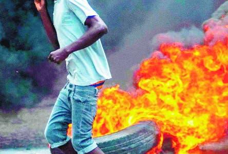 -FOTODELDIA- STO01. PUERTO PRÍNCIPE (HAITÍ), 10/06/2019.- Un hombre pasa frente a una barricada en llamas este lunes, en Puerto Príncipe. La capital de Haití se encuentra este lunes prácticamente paralizada tras las violentas manifestaciones de ayer convocadas por la oposición en varias ciudades para exigir la dimisión del presidente Jovenel Moise y que dejaron varios muertos, según los organizadores de las protestas. EFE/Jean Marc Herve Abelard