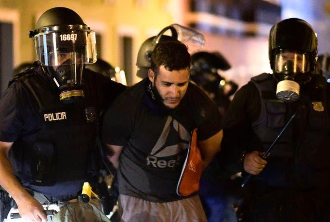 1. La policía arresta a un manifestante durante los enfrentamientos que exigen la renuncia del gobernador Ricardo Rosselló en San Juan, Puerto Rico, el lunes 22 de julio de 2019. Los manifestantes exigen que el gobernador renuncie tras la filtración de una charla en línea, ofensiva y obscena, entre él y sus asesores, lo que desencadenó la crisis. (AP Foto/Carlos Giusti)