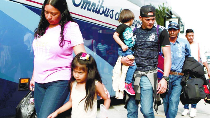 """Central American migrants prepare to board a bus as they voluntarily return to their countries, in Ciudad Juarez, Mexico, Tuesday, July 2, 2019. Dozens of Central Americans who had been returned to the border city of Juarez to await the outcome of their U.S. asylum claims are being bused back to their countries Tuesday by Mexican authorities, a first for that size group of people in the program commonly known as """"remain in Mexico."""" (AP Photo/Christian Chavez)"""