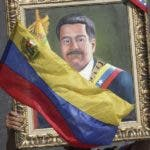 FILE - This May 1, 2019 file photo shows a government supporter holding a framed image of Venezuelan President Nicolas Maduro during an anti-imperialist rally, in Caracas, Venezuela. The Trump administration is facing a July 27, 2019 deadline to renew a license granting Chevron permission to continue operating in Venezuela despite U.S. sanctions aimed at ousting Maduro by choking off revenue from the world's largest crude reserves. (AP Photo/Boris Vergara, File)