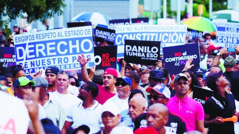 Decenas de personas participan en una protesta contra la posible reforma constitucional que permitiría nuevamente la reelección del presidente de R. Dominicana, Danilo Medina,  frente al Congreso Nacional (bicameral), en Santo Domingo (República Dominicana). El Congreso Nacional Santo Domingo Rep.  Dom. 12 de julio de 2019. Foto Pedro Sosa