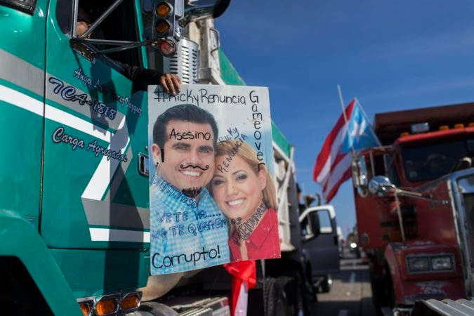 """13. Demonstrators carry a defaced poster of Governor Ricardo Rossello and his wife, with inscriptions that read in Spanish """"Corrupt, murderer, Ricky quit, liar, go, we do not want you"""" as they march on Las Americas highway demanding the resignation of Governor Rossello, in San Juan, Puerto Rico, Monday, July 22, 2019. Protesters are demanding Rossello step down for his involvement in a private chat in which I have used profanities to describe an ex-New York City councilwoman and a federal control board overseeing the island's finance . (AP Photo / Dennis M. Rivera Pichardo)"""