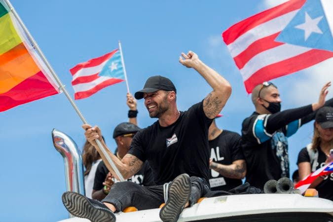 14. Ricky Martin, flying a gay pride flag, joins a protest to demand the resignation of Governor Ricardo Rossello from office, in San Juan, Puerto Rico, Monday, July 22, 2019. Protesters are demanding Rossello step down for his involvement in a private chat in which he used profanities to describe an ex-New York City councilwoman and a federal control board overseeing the island's finance. (AP Photo/Dennis M. Rivera Pichardo)