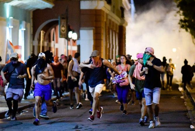 4. Demonstrators affected by tear gas thrown by the police run during clashes in San Juan, Puerto Rico, Monday, July 22, 2019.  Protesters are demanding Rossello step down following the leak of an offensive, obscenity-laden online chat between him and his advisers that triggered the crisis.  (AP Photo/Carlos Giusti)