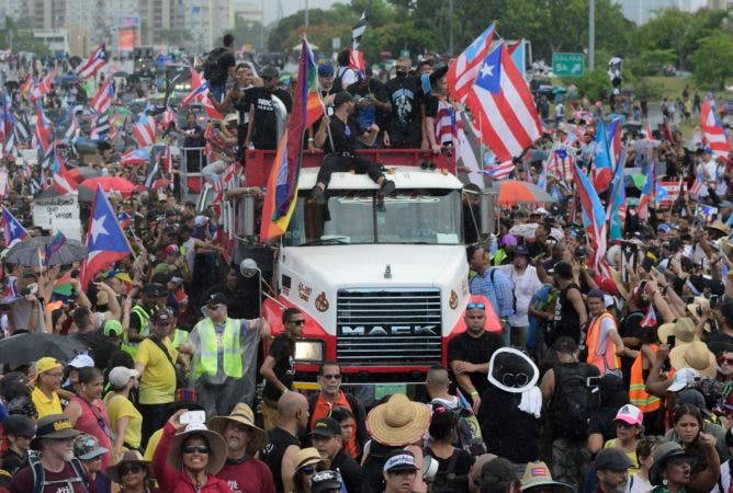 6. Puerto Rican singer Ricky Martin, front atop truck, participates with other local celebrities in a protest demanding the resignation of governor Ricardo Rossello in San Juan, Puerto Rico, Monday, July 22, 2019. Protesters are demanding Rossello step down for his involvement in a private chat in which he used profanities to describe an ex-New York City councilwoman and a federal control board overseeing the island's finance. (AP Photo/Carlos Giusti)