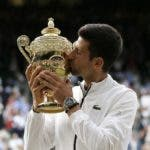 Serbia's Novak Djokovic kisses the trophy after defeating Switzerland's Roger Federer in the men's singles final match of the Wimbledon Tennis Championships in London, Sunday, July 14, 2019. (AP Photo/Tim Ireland)