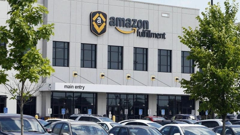 """Workers at an Amazon Fulfillment warehouse, shown Monday, July 8, 2019 in Shakopee, Minn., say they'll hit the online retail and entertainment giant with a brief strike next Monday. They're targeting """"Prime Day"""" in a continuing push to improve pay and working conditions for the facility's heavily East African workforce. (AP Photo/Jim Mone)"""