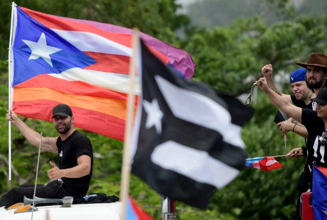 7. Puerto Rican singer Ricky Martin holds a Puerto Rico flag as he participates in a protest demanding the resignation of governor Ricardo Rossello, in San Juan, Puerto Rico, Friday, July 19, 2019. Protesters are demanding Rossello step down for his involvement in a private chat in which he used profanities to describe an ex-New York City councilwoman and a federal control board overseeing the island's finance. (AP Photo/Carlos Giusti)