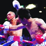 Manny Pacquiao, right, punches the mouthpiece from Keith Thurman during the fifth round of a welterweight title fight Saturday, July 20, 2019, in Las Vegas. (AP Photo/John Locher)