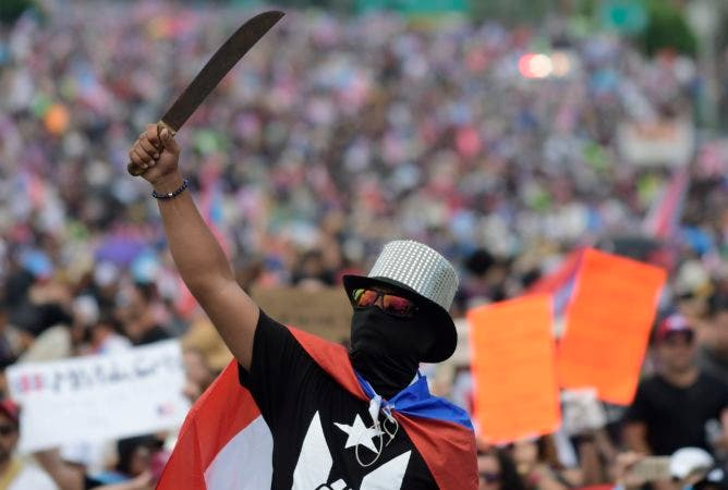8. A demonstrator brandishes a machete during a march on Las Americas highway to demand the resignation of governor Ricardo Rossello, in San Juan, Puerto Rico, Monday, July 22, 2019. Protesters are demanding Rossello step down for his involvement in a private chat in which he used profanities to describe an ex-New York City councilwoman and a federal control board overseeing the island's finance. (AP Photo/Carlos Giusti)
