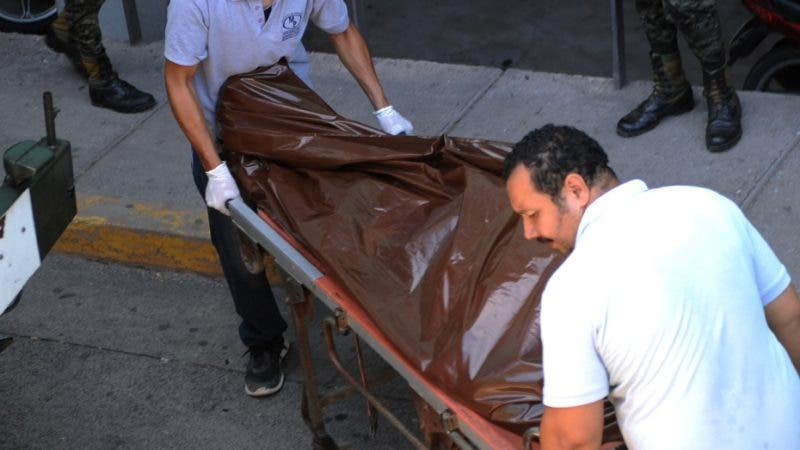 """Forensic personnel carry the corpse of the president of Honduras' Taxi Association (Ataxis), Oscar Castillo, shot dead by unknown gunmen in Tegucigalpa on August 18, 2015. Castillo had denounced several times that taxi and bus drivers are forced by criminal gangs to pay them a """"war tax"""". In the first half of the year, 50 people have been killed -- 17 of them drivers -- and 25 wounded in attacks on public transport, according to the National Human Rights Commission. Violence in Central America is being fueled by a turf war between the region's two main gangs, Mara Salvatrucha (MS-13) and Mara 18, which have carved up the lucrative business of drug trafficking, extortion and murder for hire in Honduras, El Salvador and Guatemala.   AFP PHOTO / ORLANDO SIERRA"""