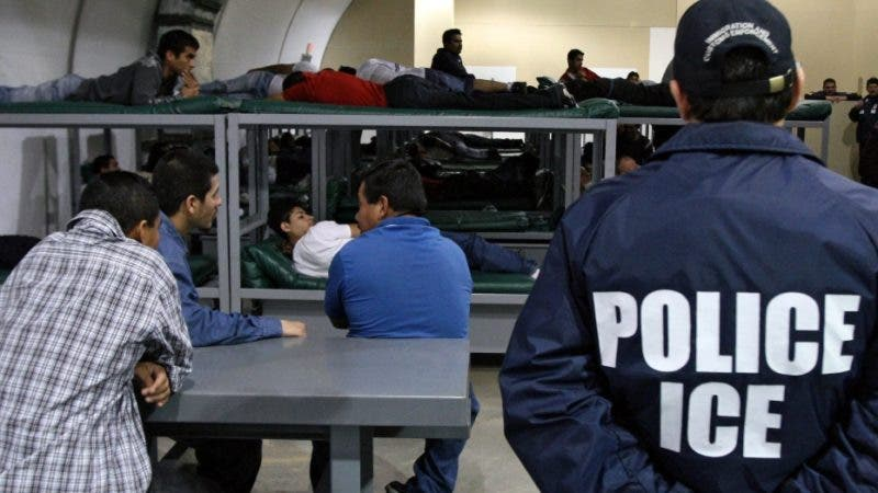 TO GO WITH AFP STORY BY CARLOS MARIO MARQUEZ An Immigration and Customs Enforcement (ICE) officer guards a group of 116 Salvadorean immigrants that wait to be deported,at Willacy Detention facility in Raymondville, Texas on December 18, 2008 early morning. The Willacy facility is used by the US Immigration and Customs Enforcement agency (ICE) to keep illegal immigrants in detention before they are deported. Today, 116 Salvadorean nationals --83 men and 33 women-- were woken up at 4 a.m. and transported in buses under strict surveillance to Harlengen's airport to be taken back to El Salvador.  AFP PHOTO/ Jose CABEZAS