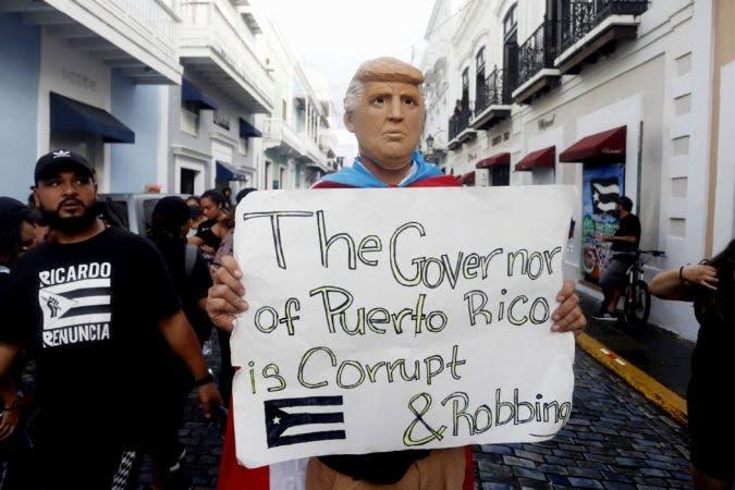 """9. -FOTODELDIA- -FOTODELDIA- AME9060. SAN JUAN (PUERTO RICO), 22/07/2019.- Un hombre disfrazado del presidente estadounidense, Donald Trump, sostiene una pancarta que dice """"El gobernador de Puerto Rico es corrupto y roba"""", en San Juan, Puerto Rico. Algunos de los cantantes más conocidos de Puerto Rico como Daddy Yankee, Ricky Martin, Bad Bunny, Olga Tañón, Kany García, Tommy Torres o Residente, entre otros, asistieron de nuevo a una segunda macromanifestación que se celebró este lunes para pedir la dimisión del gobernador de la isla, Ricardo Rosselló, por el escándalo político desatado por su implicación en un polémico chat privado. EFE/Thais Llorca"""