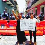 MIA59. SAN JUAN (PUERTO RICO), 16/07/2019.- Dos manifestantes sostienen una pancarta que pide dimisión del gobernador, este martes frente a unos agentes de policía en San Juan (Puerto Rico). El gobernador de Puerto Rico, Ricardo Rosselló, dijo este martes que la Policía de la isla caribeña aguantó más de lo que puede esperarse ante las agresiones sufridas el lunes por parte de los manifestantes que exigían su renuncia por su participación en el chat de miembros del Ejecutivo. EFE/Thais Llorca