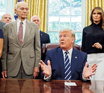 President Donald Trump, accompanied by Apollo 11 astronauts Michael Collins, left, and Buzz Aldrin, right, with Vice President Mike Pence and first lady Melania Trump, speaks during a photo opportunity commemorating the 50th anniversary of the Apollo 11 moon landing, in the Oval Office of the White House, Friday, July 19, 2019, in Washington. (AP Photo/Alex Brandon)