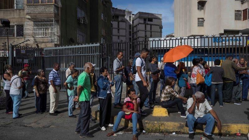 Un grupo de personas hace fila para ingresar a un banco mientras varias zonas continúan sin luz este martes, en Caracas (Venezuela). Al menos cinco estados de Venezuela continúan este martes sin electricidad desde que se produjera un apagón general la tarde del lunes, mientras que el Gobierno informa de avances en la reconexión del servicio en al menos nueve regiones. EFE/ Miguel Gutiérrez