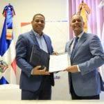 El doctor Trajano Santana y el ingeniero Armando García muestran el documento firmado