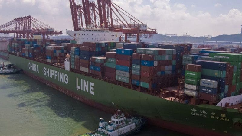 Barcos remolcadores maniobran un buque de carga en un puerto en Qingdao, en el este de China, el 6 de agosto de 2019. (Chinatopix via AP)