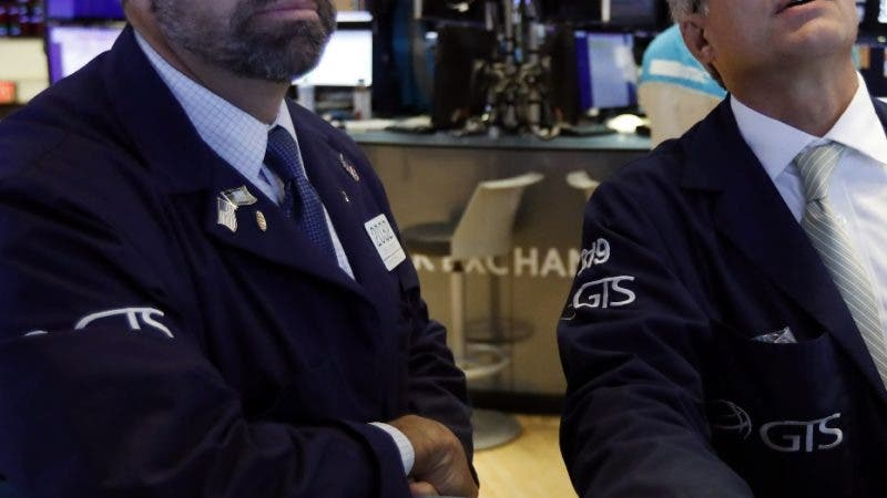 Specialists James Denaro, left, and Anthony Rinaldi work on the floor of the New York Stock Exchange, Tuesday, Aug. 13, 2019. Stocks tore higher Tuesday, continuing their roller-coaster ways, after the latest turn in the U.S.-China trade war flipped investors back to buying mode. (AP Photo/Richard Drew)