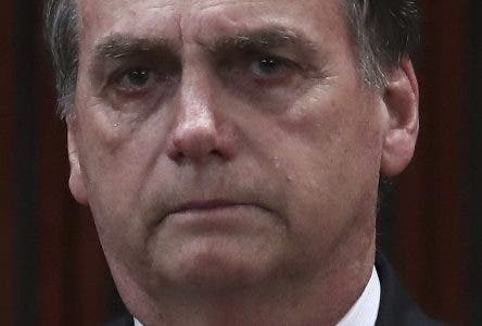Brazil's President-elect Jair Bolsonaro cries during the playing of the national anthem at a ceremony officially confirming his election as Brazil's president of the republic, at the Supreme Electoral Court, in Brasilia Brazil, Monday, Dec. 10, 2018. Bolsonaro will be sworn in as Brazil's next president on Jan. 1. (AP Photo/Eraldo Peres)