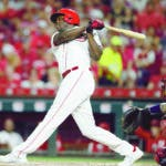 Cincinnati Reds' Aristides Aquino follows through on a two-run home run off St. Louis Cardinals starting pitcher Adam Wainwright during the sixth inning of a baseball game, Friday, Aug. 16, 2019, in Cincinnati. (AP Photo/Gary Landers)