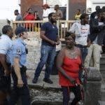 Agentes de la policía piden a la gente que abandone la zona mientras investigan un tiroteo el miércoles 14 de agosto de 2019, en el vecindario Nicetown, Filadelfia. (AP Foto/Matt Rourke)