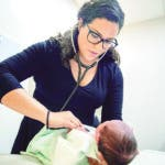 In this Tuesday, Aug. 13, 2019, photo, Dr. Jasmine Saavedra, a pediatrician at Esperanza Health Centers whose parents emigrated from Mexico in the 1980s, examines Alondra Marquez, a newborn baby in her clinic in Chicago. Doctors and public health experts warn of poor health outcomes and rising costs they say will come from sweeping changes that would deny green cards to many immigrants who use Medicaid, as well as food stamps and other forms of public assistance. Saavedra is convinced that if new Trump administration criteria were in effect for her parents three decades ago, she wouldn't have become a pediatrician. (AP Photo/Amr Alfiky)