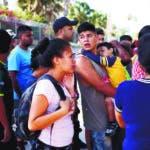Archivo - En esta fotografía de archivo del 1 de agosto de 2019, migrantes hacen fila en Matamoros, México, para recibir una comida donada por voluntarios estadounidenses, en el puente Puerto México que cruza hacia Brownsville, Texas. (AP Foto/Emilio Espejel. Archivo)