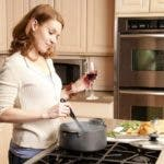 Single Caucasion Adult Woman Cooking in Kitchen With Wine