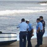 Puerto Rican police officers watch the boat used by a group of illegal migrants from the Dominican Republic that reach the west coast town of Rincon, Puerto Rico, Thursday, Jan. 29, 2004. U.S. authorities detained 36 Dominicans early Thursday in two separate incidents as the number of illegal migrants that been detained in the past four months is nearing the total caught in the entire previous year. Meanwhile, a two-day strike in the Dominican Republic began Wednesday to protest the worst economic crisis in decades. (AP Photo/Javier Gonzalez) ** PUERTO RICO OUT **