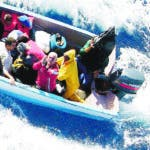 In this photo released on Wednesday, Dec. 1, 2004 by the U.S. Coast Guard, an unidentified illegal migrant, third right, asks for mercy before his wooden boat is intercepted by a Coast Guard cutter about one mile west of Mona Island, Puerto Rico, on Monday, Nov. 29, 2004. The 12 Cubans and two Dominicans in the boat were returned to the Dominican Republic where they had embarked. U.S. authorities have detained at least 130 migrants trying to reach the U.S. Caribbean territory in the last three days. (AP Photo/U.S. Coast Guard)
