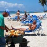 Vendedor de frutas y turistas en la playa del Hotel Coral Costa Caribe, en Juan Dolio. Hoy/ Rafael Segura Imagen Digital/ 27/03/010