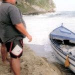 Residents look at at a boat that washed up on El Pastillo beach which was carrying illegal Dominican migrants and landed off the coast of Isabela, Puerto Rico, Wednesday, March 8, 2000. An unknown number of migrants from this boat made it safely to shore. Another boat carrying an estimated 63 migrants broke apart in heavy surf in the same area, killing at least seven people and leaving dozens missing. (AP Photo/Javier Gonzalez) PUERTO RICO OUT