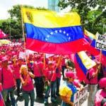 """AME190. CARACAS (VENEZUELA), 21/09/2019.- Personas adeptas al chavismo participan en una marcha este sábado para consignar ante la Vicepresidencia de Venezuela 13.287.742 millones de firmas contra el bloqueo de EE.UU. a los bienes estatales venezolanos, en Caracas (Venezuela). La vicepresidenta de Venezuela, Delcy Rodríguez, indicó este sábado que denunciará la supuesta vinculación del jefe del Parlamento, Juan Guaidó, con el grupo criminal colombiano """"Los Rastrojos"""" ante las Naciones Unidas, a donde también llevará más de 13 millones de firmas contra el """"bloqueo"""" de EE.UU. """"Están allí las evidencias de la conexión entre la organización criminal de Guaidó con la banda 'Los Rastrojos' y el Gobierno de Iván Duque"""", dijo al término de una marcha que realizó el chavismo. EFE/ MIGUEL GUTIERREZ"""