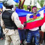 Anti-government protesters hold a Haitian flag before security forces during a march called by the artist community in Port-au-Prince, Haiti, Sunday, Oct. 20, 2019. Anger over corruption, inflation and scarcity of basic goods including fuel has led to weeks of demonstrations asking for the resignation of President Jovenel Moise that have paralyzed the country. (AP Photo/Rebecca Blackwell)