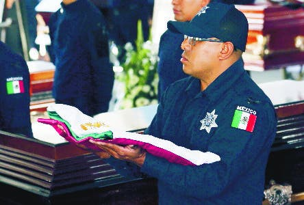 Police stand vigil next to the coffins containing the remains of Mexican police officers killed in an apparent cartel ambush, during a memorial service in Morelia, Mexico, Tuesday, Oct. 15, 2019. The families of the 13 slain police officers gathered to mourn their loved ones outside a funeral home in the western state of Michoacan on Tuesday, many of them angry at the government and police chiefs they believe sent them to a certain death. (AP Photo/Marco Ugarte)