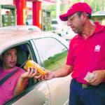 En esta imagen del 8 de octubre de 2019, el dependiente de gasolinera Orlando Godoy recibe un paquete de harina de maíz como pago tras llenar el depósito de un conductor, que cuesta una fracción diminuta de un centavo estadounidense, en San Antonio de los Altos, a las afueras de Caracas, Venezuela. La economía está tan hundida que los conductores pagan ahora con algo de comida, una chocolatina o un cigarrillo. (AP Foto/Ariana Cubillos)