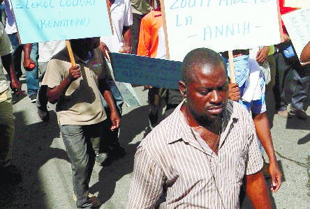Several hundred protesters march carrying signs in Creole calling for President Jovenel Moïse to resign so that schools can reopen, in Port-au-Prince, Haiti, Monday, Oct. 21, 2019. Many schools around the country have now been closed for more than a month as protests block roads and paralyze the economy. The United Nations said in early October that roughly 2 million children were unable to go to school due to the unrest. (AP Photo/Rebecca Blackwell)