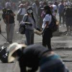 AME9918. QUITO (ECUADOR), 14/10/2019.- Un grupo de personas usa mascarillas sanitarias en las labores de limpieza de los escombros dejados por los disturbios durante las manifestaciones que cesaron tras los acuerdos entre el Gobierno y manifestantes, hoy lunes en Quito. Once días después de intensas protestas en Quito, este lunes la capital ecuatoriana parecía apresurarse por recuperar la normalidad y oportunistas como los vendedores de mascarillas apuraban sus últimos cartuchos para redondear unas ventas que superan los 500 dólares de promedio. EFE/ Bienvenido Velasco