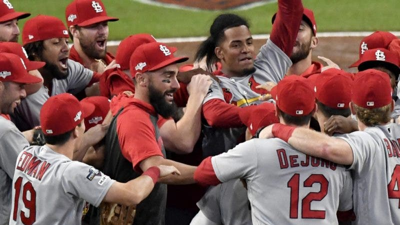 St. Louis Cardinals relief pitcher Genesis Cabrera waves his hat in the air as he celebrates with teammates after the Cardinals beat the Atlanta Braves 13-1 in Game 5 of their National League Division Series baseball game Wednesday, Oct. 9, 2019, in Atlanta. (AP Photo/Danny Karnik)