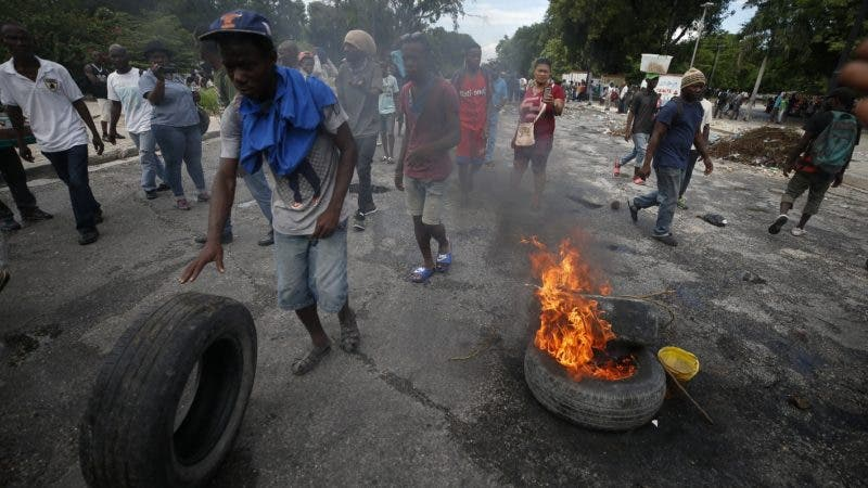 Protestors calling for the resignation of Haitian President Jovenel Moise burn tires in a park outside the National Palace in Port-au-Prince, Haiti, Tuesday, Oct. 1, 2019. While there were sporadic demonstrations on Tuesday, another protest scheduled for Wednesday threatened to once again paralyze Haiti's capital and nearby communities, which have endured violent demonstrations for nearly a month as anger grows over corruption, spiraling inflation and dwindling supplies of food and gasoline. (AP Photo/Rebecca Blackwell)