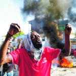 An anti-government protester shouts that Haitian President Jovenel Moise must step down in Port-au-Prince, Haiti, Monday, Oct. 7, 2019. The country enters its fourth week of protests that have paralyzed the economy and shuttered schools. (AP Photo/Rebecca Blackwell)