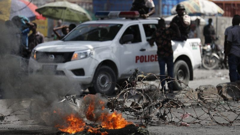 A protester talks with police next to a barricade of barbed wire and burning tires, set up by anti-government protesters who are trying to paralyze transport and commerce to pressure President Jovenel Moise to resign, in Port-au-Prince, Haiti, Tuesday, Oct. 8, 2019.  (AP Photo/Rebecca Blackwell)