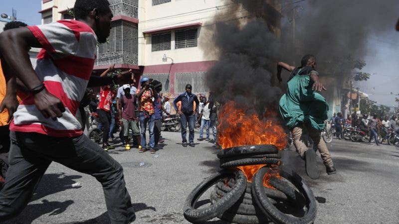 Demonstrators jump over a burning barricade during anti-government protests in Port-au-Prince, Haiti, Friday, Oct. 11, 2019. Protesters burned tires and spilled oil on streets in parts of Haiti's capital as they renewed their call for the resignation of President Jovenel Moïse just hours after a journalist was shot to death. (AP Photo/Rebecca Blackwell)